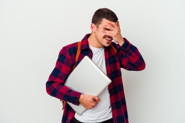 Młody student kaukaski mężczyzna trzyma laptop na białym tle mrugając do aparatu przez palce, zawstydzony zakrywający twarz.