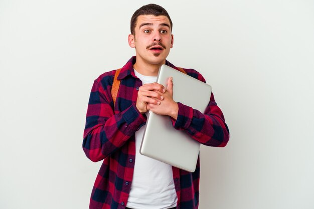Młody student kaukaski mężczyzna trzyma laptop na białym tle na białej ścianie trzyma ręce pod brodą, patrzy szczęśliwie na bok.