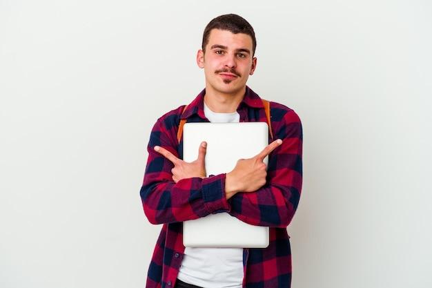 Młody student kaukaski mężczyzna trzyma laptopa na białym tle na białe punkty z boku, próbuje wybrać jedną z dwóch opcji.