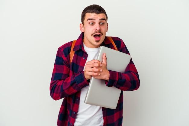 Młody student kaukaski mężczyzna trzyma laptopa na białym tle na białej ścianie, modląc się o szczęście, zdumiony i otwierając usta patrząc do przodu