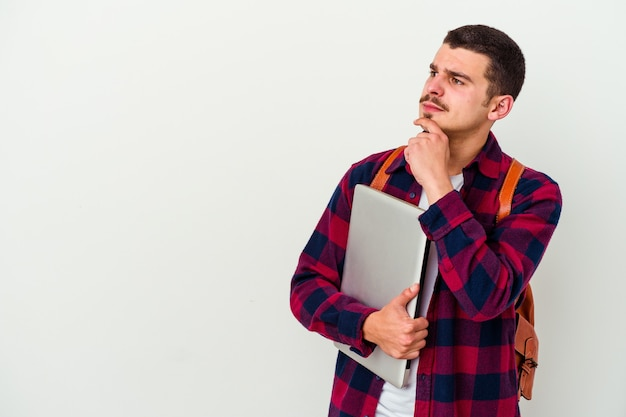 Młody student kaukaski mężczyzna trzyma laptopa na białym tle na białej ścianie, patrząc w bok z wątpliwym i sceptycznym wyrazem.