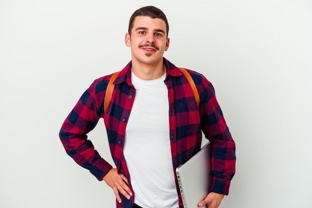 Młody student kaukaski mężczyzna trzyma laptopa na białym tle na białej ścianie pewnie trzymając ręce na biodrach.