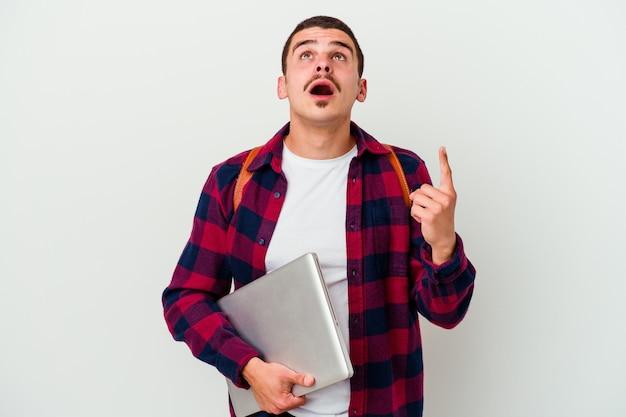 Młody student kaukaski mężczyzna trzyma laptopa na białym tle na białej ścianie, wskazując do góry z otwartymi ustami