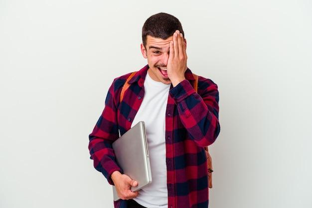 Młody student kaukaski mężczyzna trzyma laptopa na białym tle na białej ścianie zabawy obejmujące połowę twarzy dłonią.