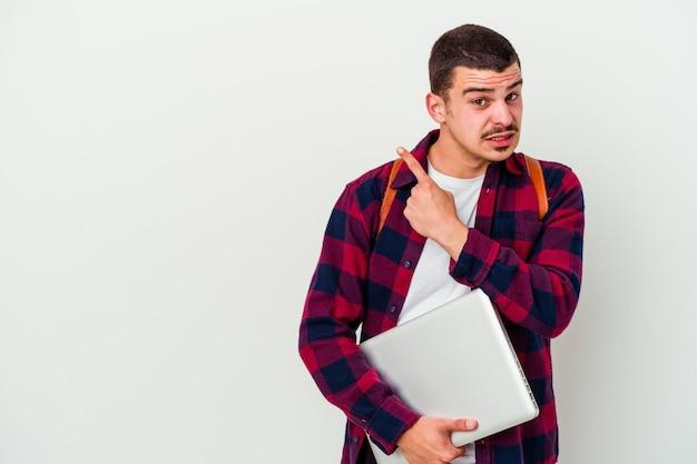 Młody student kaukaski mężczyzna trzyma laptopa na białym tle na białej ścianie zszokowany wskazując palcami wskazującymi na miejsce
