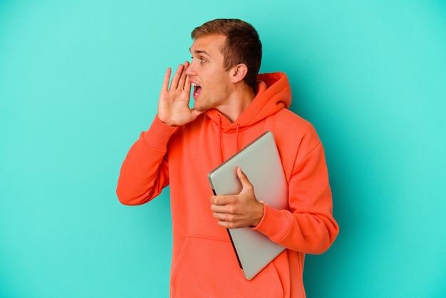 Młody student kaukaski mężczyzna trzyma laptopa na białym tle na niebiesko krzycząc i trzymając dłoń w pobliżu otwartych ust.