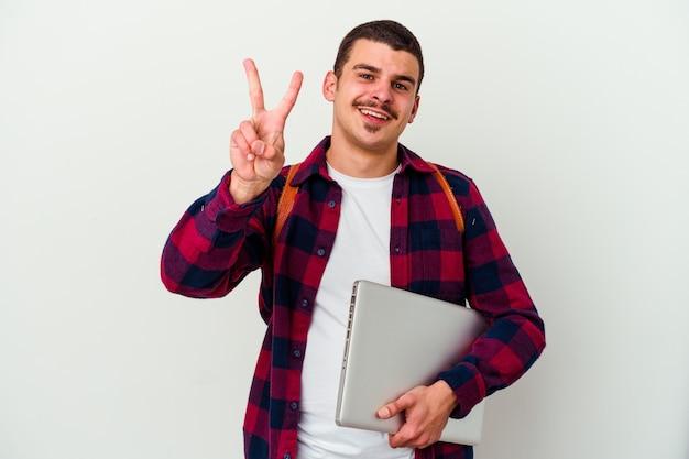 Młody student kaukaski mężczyzna trzyma laptopa na białym tle pokazując numer dwa palcami.