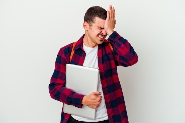 Młody student kaukaski mężczyzna trzyma laptopa na białym tle zapominając o czymś, uderzając dłonią w czoło i zamykając oczy.