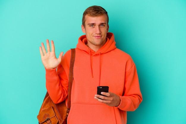 Młody student kaukaski mężczyzna trzyma telefon komórkowy na białym tle na niebieskiej ścianie uśmiechnięty wesoły pokazując numer pięć palcami.