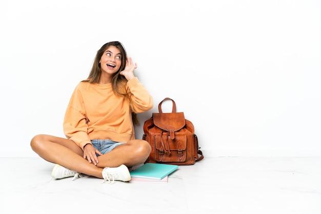 Młody student kobieta siedzi na podłodze z laptopem na białym tle na białej ścianie, słuchając czegoś, kładąc rękę na uchu