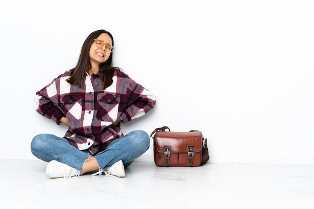 Młody student kobiety siedzącej na podłodze cierpiących na bóle pleców za to, że podjął wysiłek