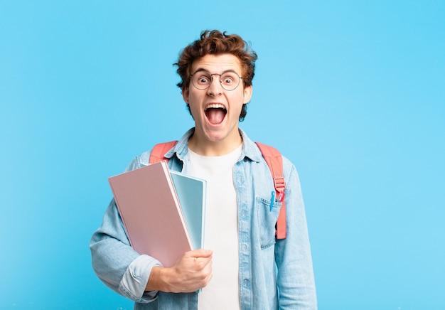 """Młody student krzyczy agresywnie, wygląda na bardzo rozgniewanego, sfrustrowanego, oburzonego lub zirytowanego, krzyczy """"nie"""""""