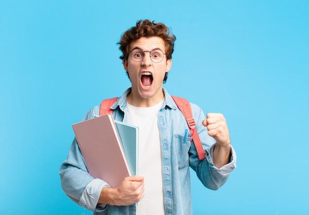 Młody student krzyczy agresywnie z gniewnym wyrazem twarzy lub z zaciśniętymi pięściami świętuje sukces