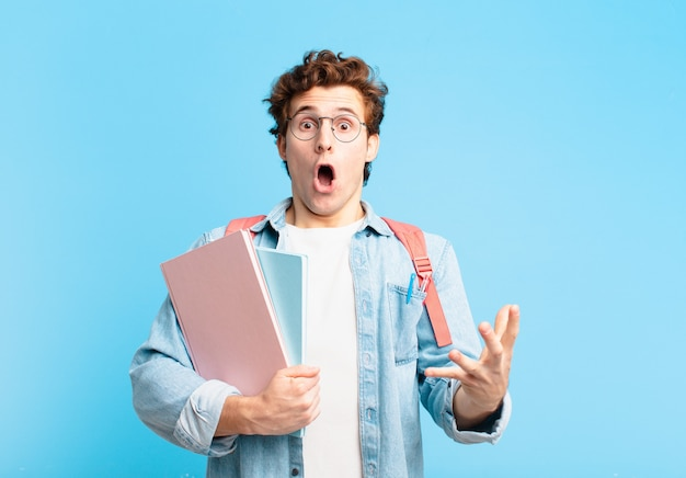 Młody student, który czuje się bardzo zszokowany i zaskoczony, niespokojny i spanikowany, o zestresowanym i przerażonym spojrzeniu