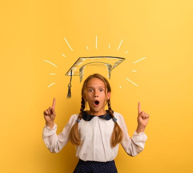 Młody student ma zszokowany wyraz twarzy i wskazuje kapelusz ukończenia szkoły. żółte tło