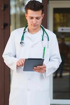 Młody student medycyny z pastylką przy szpitalnym wejściem