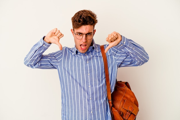 Młody student mężczyzna na białym pokazując kciuk w dół i wyrażający niechęć.