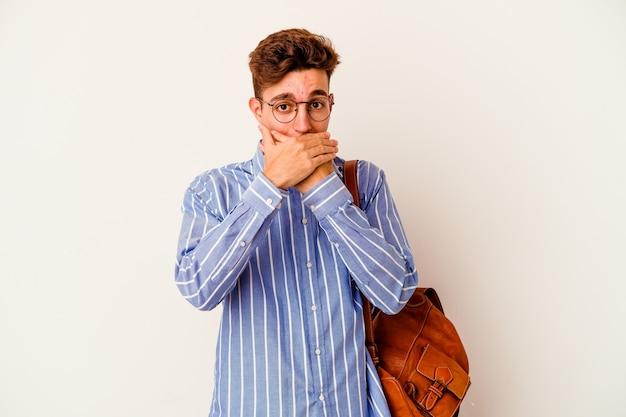 Młody student mężczyzna na białym tle na białej ścianie w szoku obejmując usta rękami.