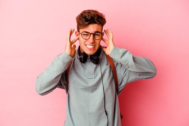 Młody student mężczyzna na białym tle na różowej ścianie obejmujące uszy rękami.