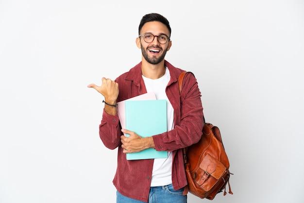 Młody student mężczyzna na białym tle wskazujący na bok, aby zaprezentować produkt