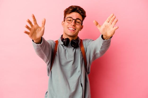 Młody student, mężczyzna na różowej ścianie, czuje się pewnie, przytulając się do przodu