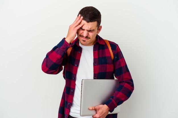 Młody student mężczyzna trzyma laptopa na białym tle na białej ścianie, dotykając świątyń i mając ból głowy