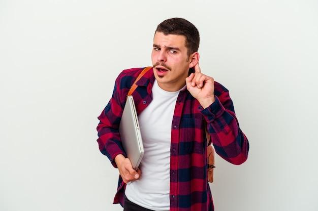 Młody student mężczyzna trzyma laptopa na białym tle na białej ścianie, próbując słuchać plotek