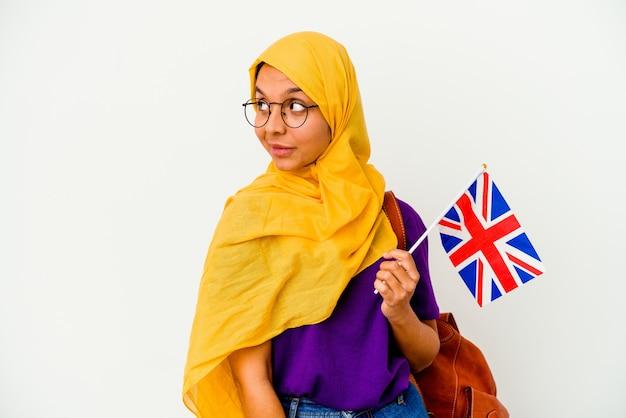 Młody student muzułmański kobieta na białym tle na białej ścianie wygląda na bok uśmiechnięty, wesoły i przyjemny.