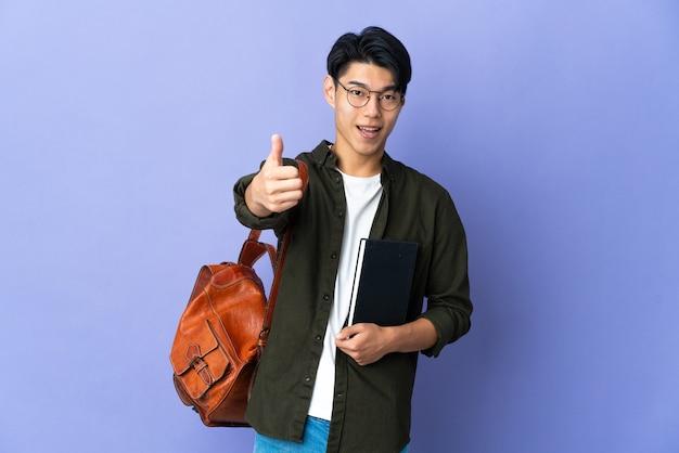 Młody student odizolowany z kciukami do góry, ponieważ wydarzyło się coś dobrego