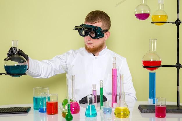 Młody student ogląda z przodu nową substancję chemiczną w okularach ochronnych