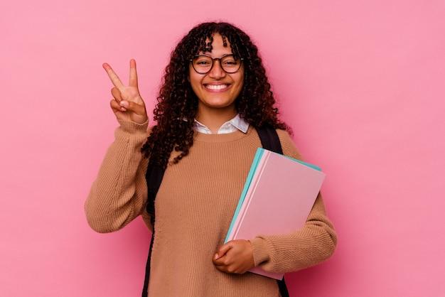 Młody student rasy mieszanej kobieta na różowym pokazując numer dwa palcami.