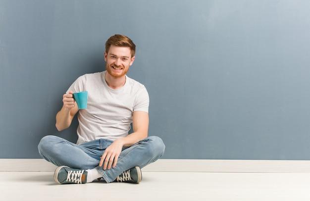 Młody student rudy mężczyzna siedzi na podłodze wesoły z wielkim uśmiechem. trzyma kubek kawy.