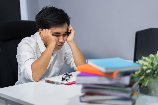Młody student siedzi i śpi na biurku z książki i laptopa