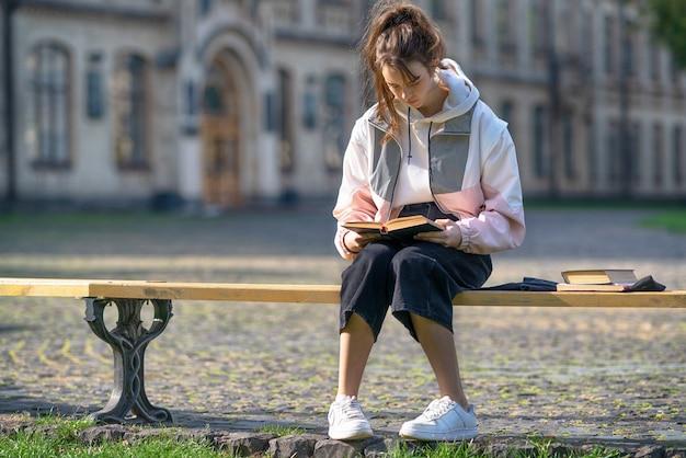 Młody student siedzi i studiuje na świeżym powietrzu