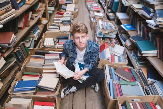 Młody student siedzi na podłodze w bibliotece publicznej z książkami na kolanach i patrząc w kamerę