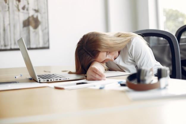 Młody student siedzi przy stole i śpi
