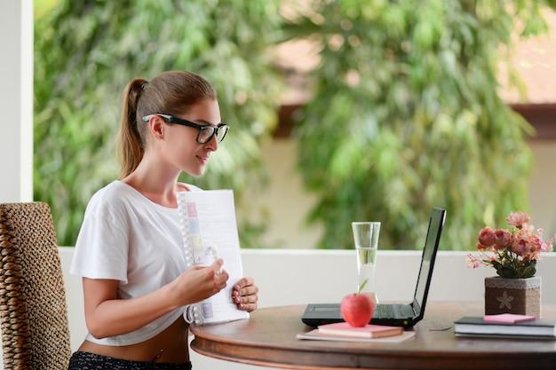 Młody student siedzi przy stole z laptopem