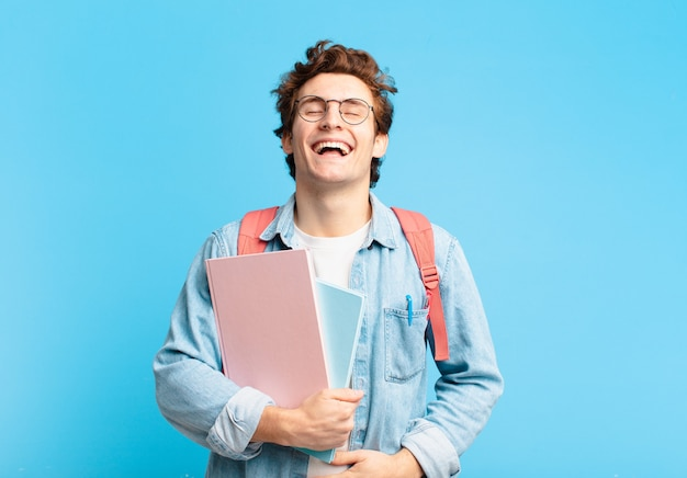 Młody student, śmiejący się głośno z jakiegoś zabawnego żartu, szczęśliwy i wesoły, dobrze się bawiący