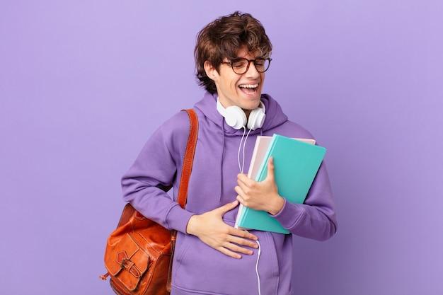 Młody student śmiejący się głośno z jakiegoś zabawnego żartu