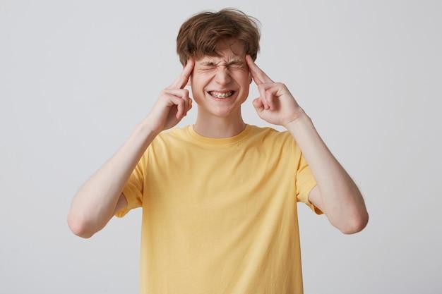 Młody student stoi nad białą ścianą i trzyma palec na głowie, z zamkniętymi oczami i bolesnym wyrazem twarzy.