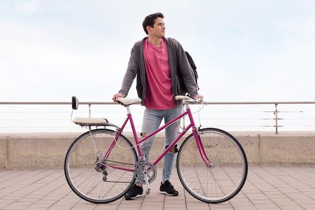 Młody student trzymający rower retro