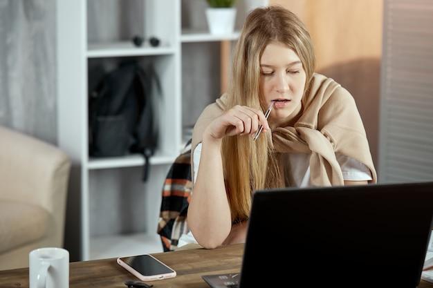 Młody student uczy się lekcji siedząc przy stole z laptopem