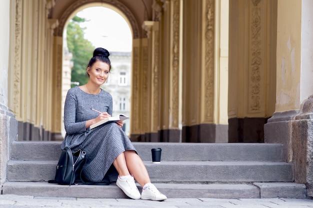 Młody student uniwersytetu dziewczyna student czyta książkę na schodach.