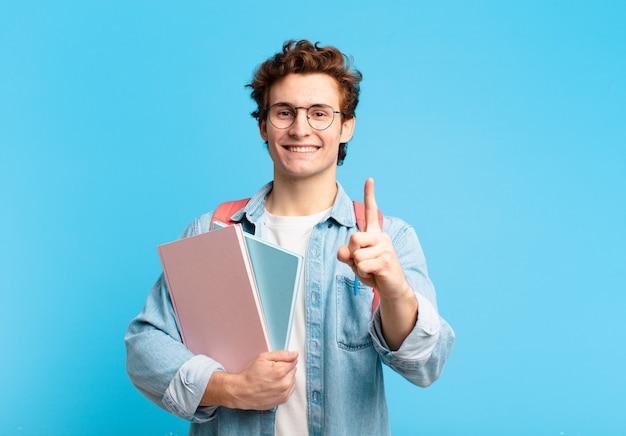 Młody student, uśmiechający się dumnie i pewnie, triumfalnie wykonując pozę numer jeden, czując się jak przywódca