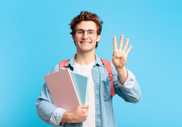 Młody student uśmiechający się i patrzący przyjaźnie, pokazujący cyfrę cztery lub czwartą z ręką do przodu, odliczający w dół