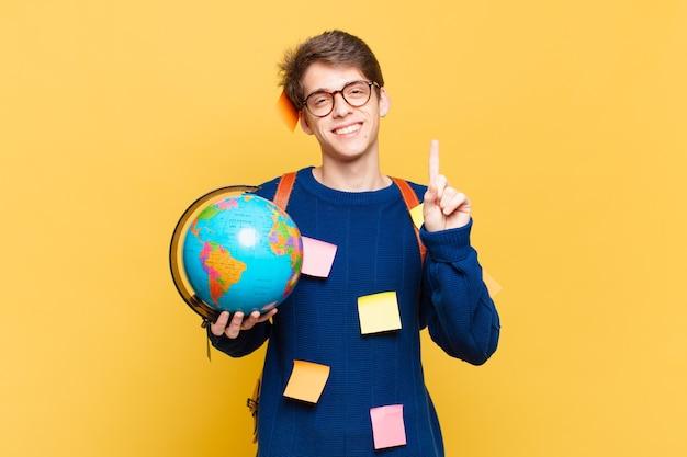 Młody student uśmiechający się i patrzący przyjaźnie, pokazujący numer jeden lub pierwszy z ręką do przodu, odliczający w dół
