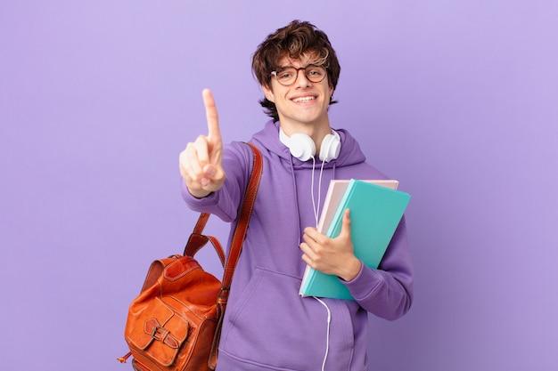 Młody student uśmiechający się i wyglądający przyjaźnie, pokazując numer jeden