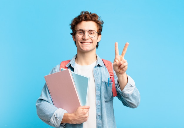 Młody student uśmiechający się i wyglądający przyjaźnie, pokazujący numer dwa lub drugi z ręką do przodu, odliczający w dół