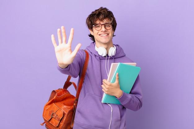 Młody student uśmiechający się i wyglądający przyjaźnie, pokazujący numer pięć