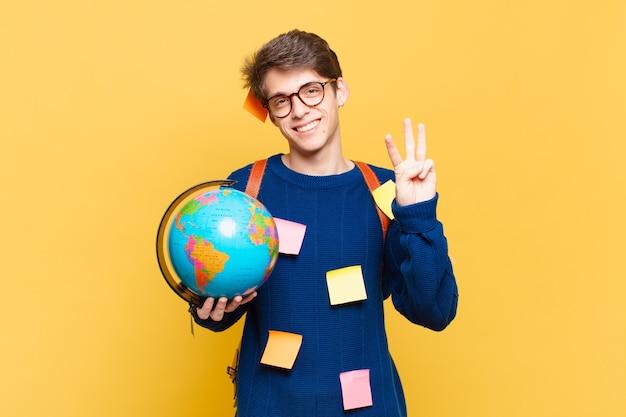 Młody student uśmiechający się i wyglądający przyjaźnie, pokazujący numer trzy lub trzeci z ręką do przodu, odliczający w dół